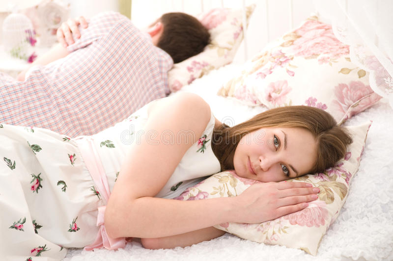 Portrait of an upset young woman lying separately stock photography