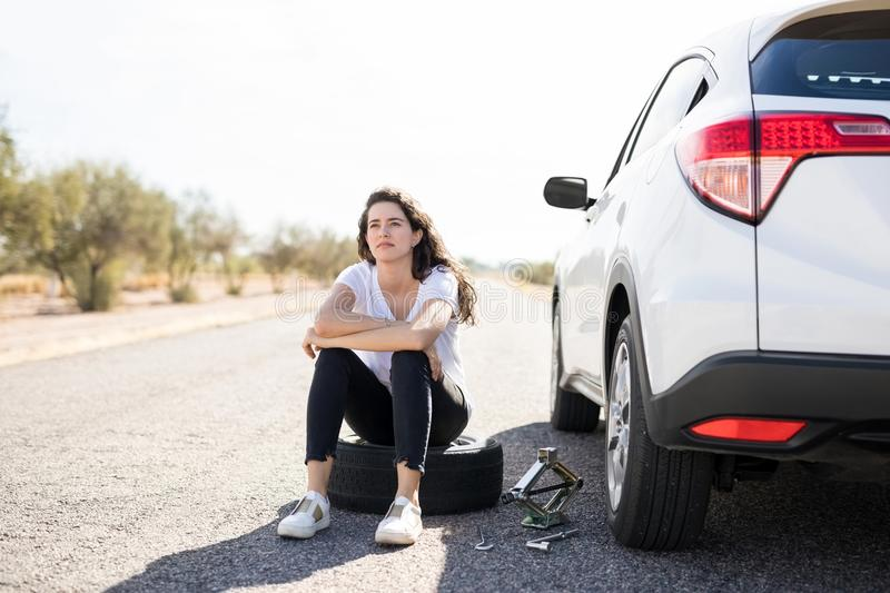 Woman looking upset with flat tyre on her car royalty free stock photography