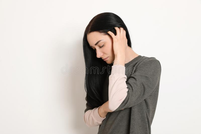Portrait of upset young woman on white background. Space for text stock image