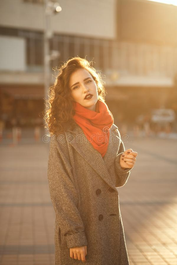Portrait urbain de belle fille de brune avec les cheveux onduleux portant la Co photographie stock