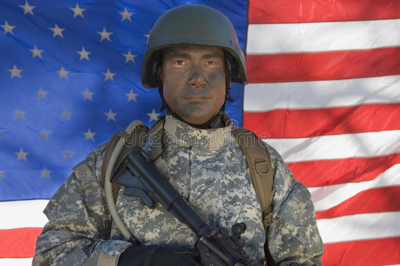 Portrait Of US Army Soldier. With gun standing in front of the American flag stock photo