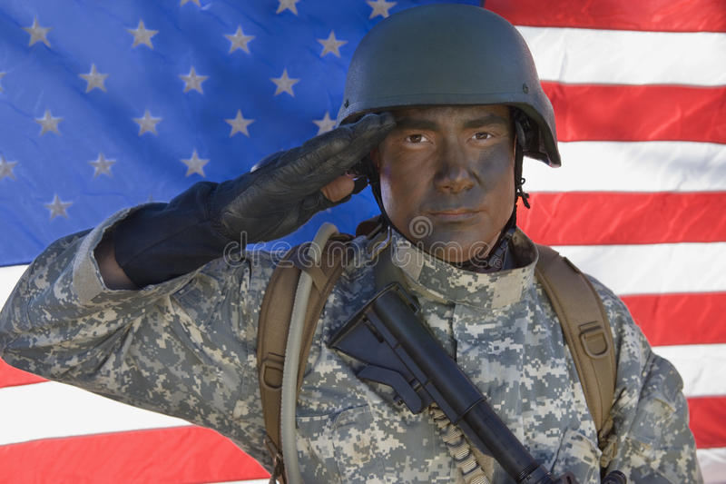 Portrait Of US Army Soldier Saluting. In front of the American flag royalty free stock photography