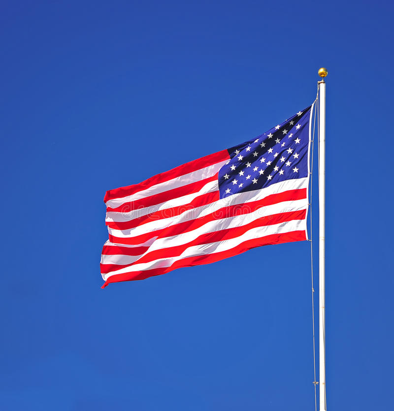 Portrait of US Flag. A US Flag flying on top of a flag pole. The wind straightens it out for visibility stock images