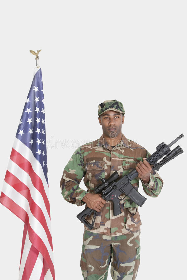 Portrait of US Marine Corps soldier with M4 assault rifle standing by American flag over gray background
