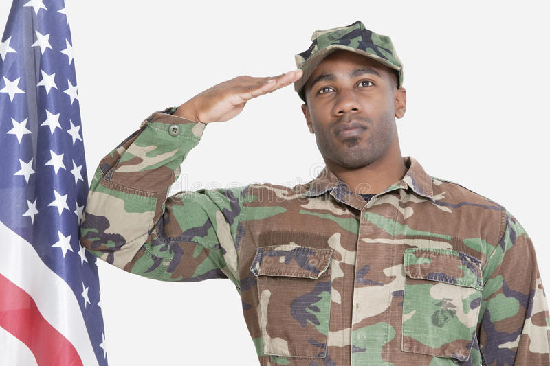 Portrait of US Marine Corps soldier saluting American flag over gray background royalty free stock image
