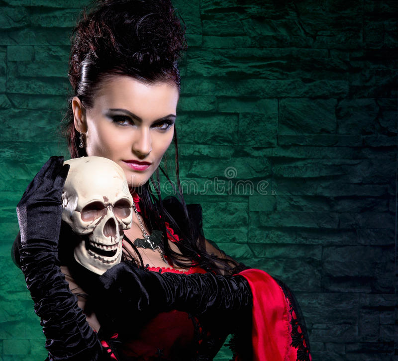 Portrait of a vampire lady holding a human skull. Halloween concept: a young and brunette lady vampire holding a human skull. The image is taken in the dungeon royalty free stock photos