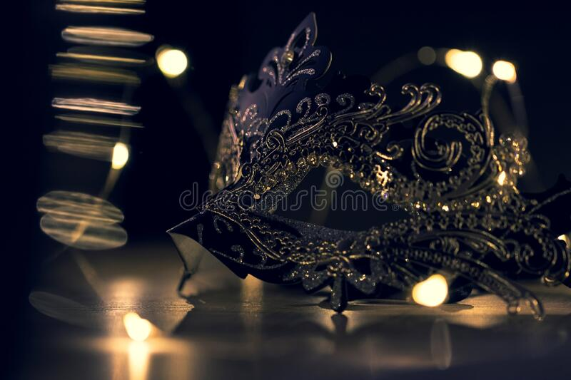 A portrait of a venetian mask on a wooden table surrounded by lights. The mask is to be worn to hide someones identity at a party. Like halloween stock photo