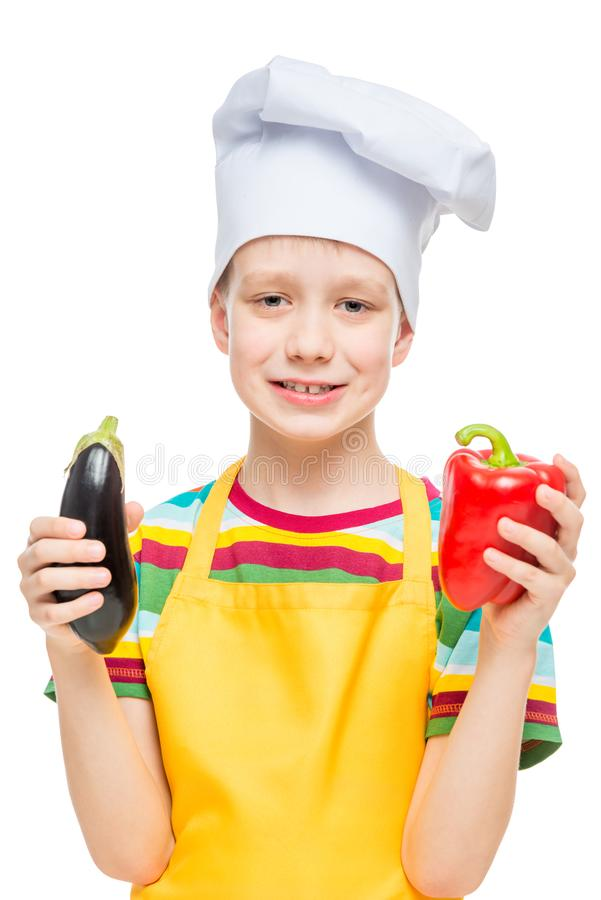 Portrait vertical d'un enfant dans un chapeau de cuisinier avec le poivre et l'aubergine sur un blanc images libres de droits