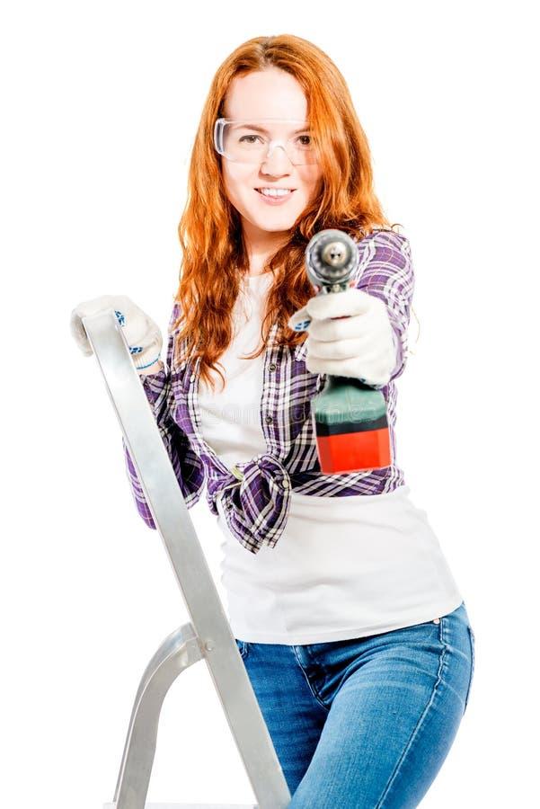 portrait vertical d'une femme sur un escabeau avec un foret photographie stock