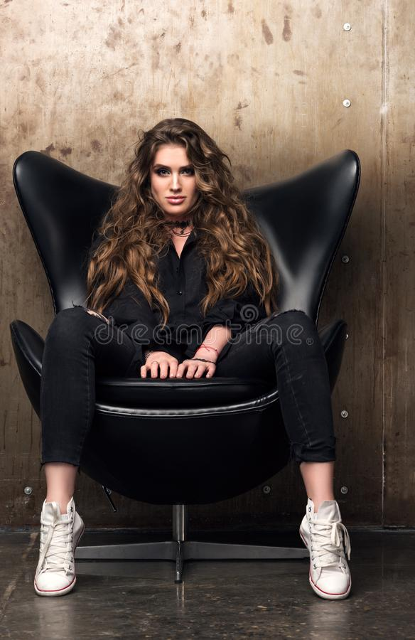Portrait vertical d'une jeune femme dominante s'asseyant dans la chaise noire photographie stock libre de droits