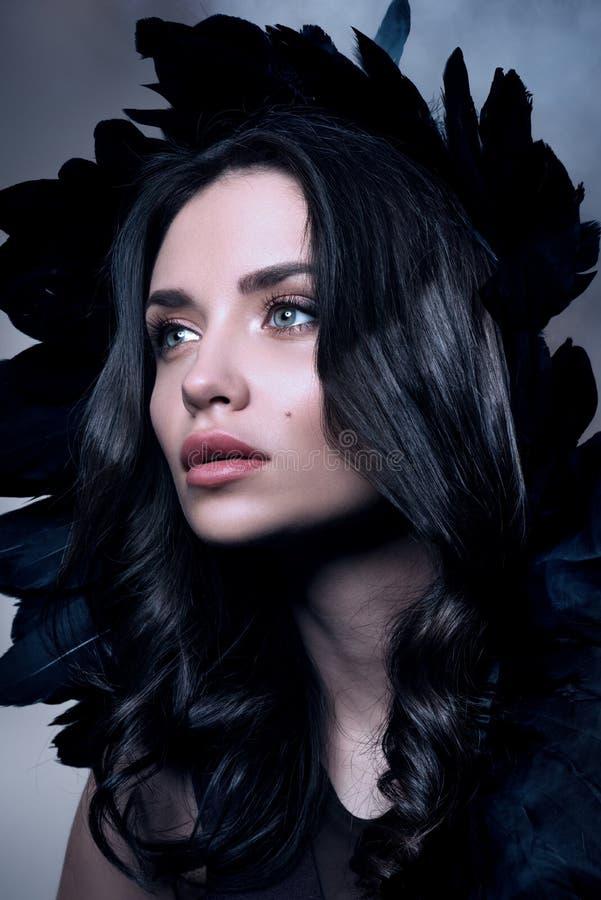 Portrait vertical de beauté dans des tons foncés Belle jeune femme dans une fumée avec les plumes noires image libre de droits