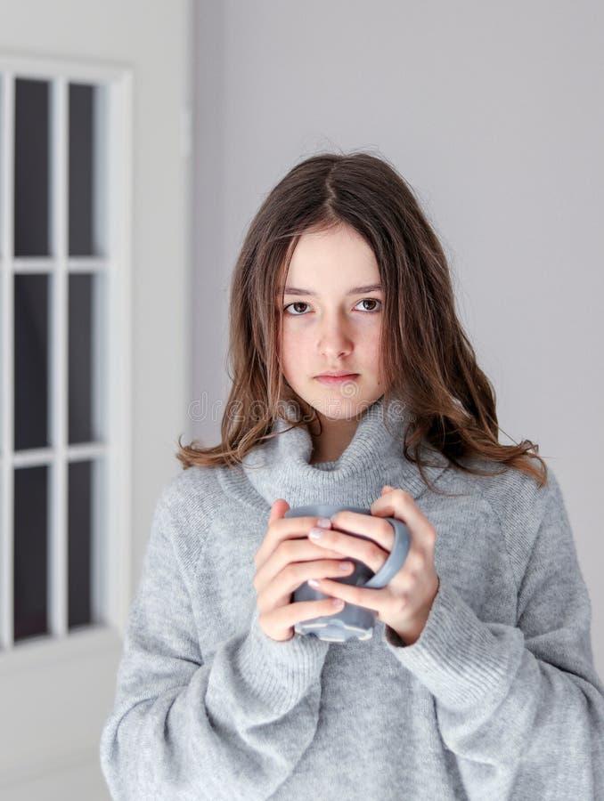 Portrait vertical de belle fille de tween dans la tasse grise chaude de participation de pull de thé regardant la caméra à la mai photos libres de droits