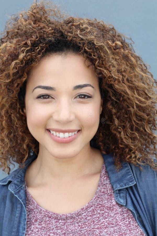 Portrait vertical de la fille latine avec le portrait de sourire de coiffure Afro blonde sur un fond bleu photographie stock libre de droits