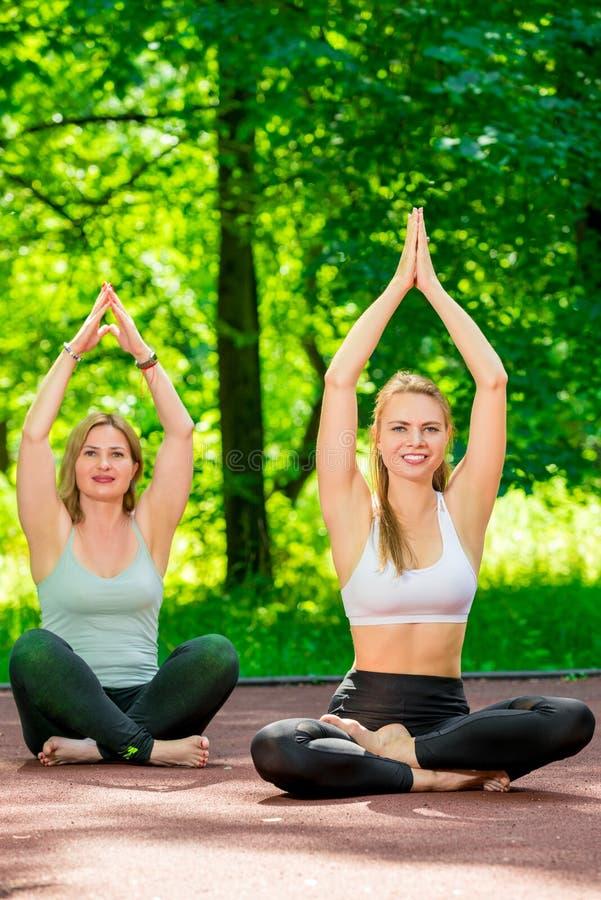 portrait vertical des femmes pendant le yoga en position de lotus photo libre de droits