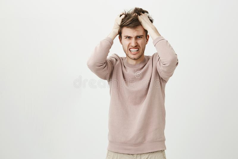 Portrait of very angry caucasian man pulling out his hair, being mad looking with furious expression at camera while. Standing against gray background stock images