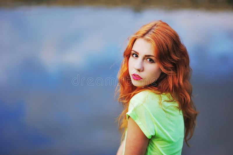 Portrait of a very beautiful brown eyed girls with bright red hair in light green dress on background lake royalty free stock photos