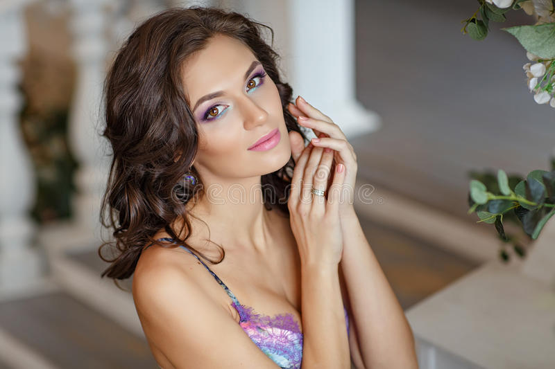 Portrait of very beautiful brunette girl in spring flower interiors with bright make-up, close-up stock photo