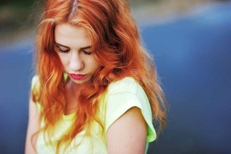 Portrait of a very beautiful girl with long red hair lowered gaz royalty free stock photo