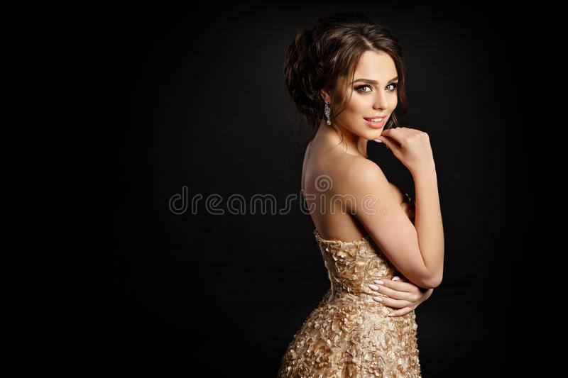 Portrait of a very beautiful girl in a gold dress on a blac. K background royalty free stock photo