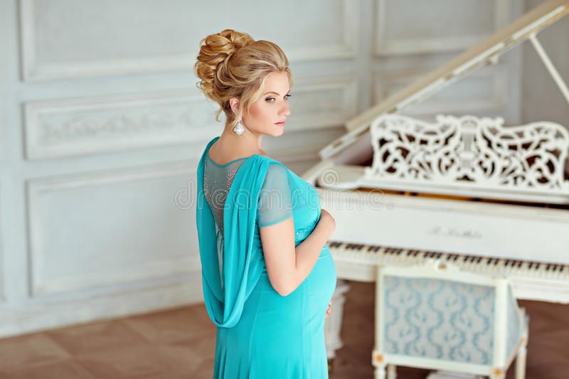 Portrait of a very beautiful, sweet, feminine and tender pregnant blonde girl with green eyes in a blue dress with rhinestones on royalty free stock images