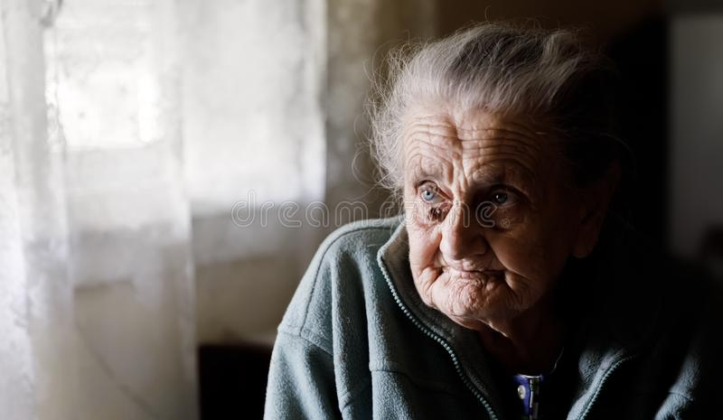 Very old tired woman. Portrait of a very old tired woman sitting near a window stock image