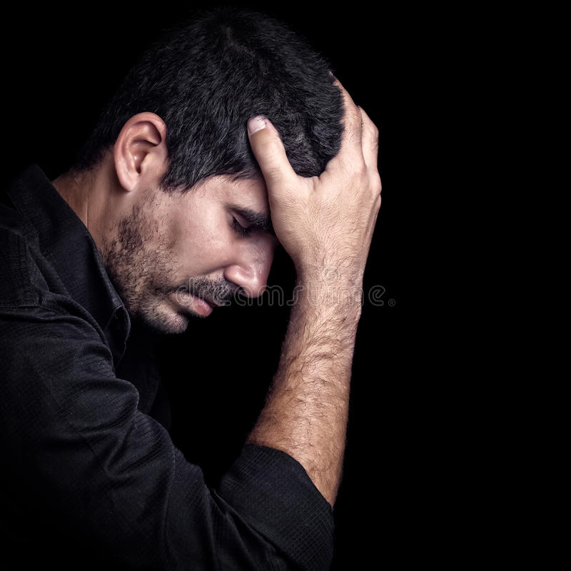 Portrait of a very sad young hispanic man. With a thoughtful expression on a black background with space for text stock photo