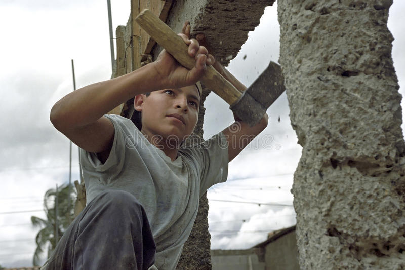 Portrait very young latino construction worker. Nicaragua, department of Nueva Segovia, Ocotal city: close-up of a boy that with a hatchet, ax, pieces of stone royalty free stock images