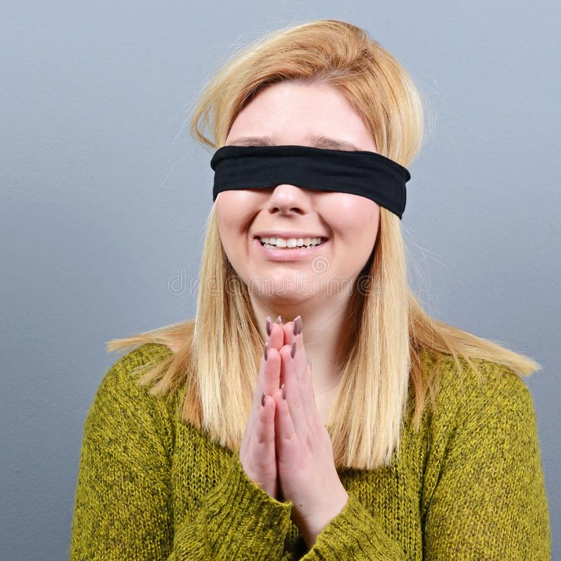 Portrait of victim of abuse and domestic violence blindfolded against gray background stock photo