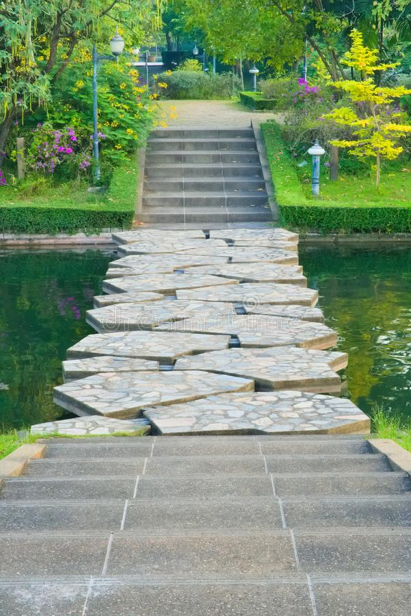 Portrait view of cement steps, leading down towards a canal stone bridge, and beyond into a lovely garden park. royalty free stock photos
