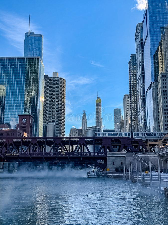 Portrait view of an elevated `el` train as it crosses the Chicago River which has steam rising up from waters stock images