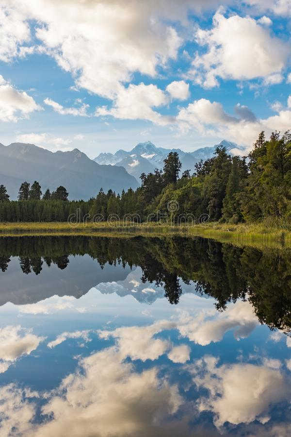 A portrait view of the incredibly beautiful Lake Matheson, New Zealand with the reflection of the stunning Southern Alps stock photo
