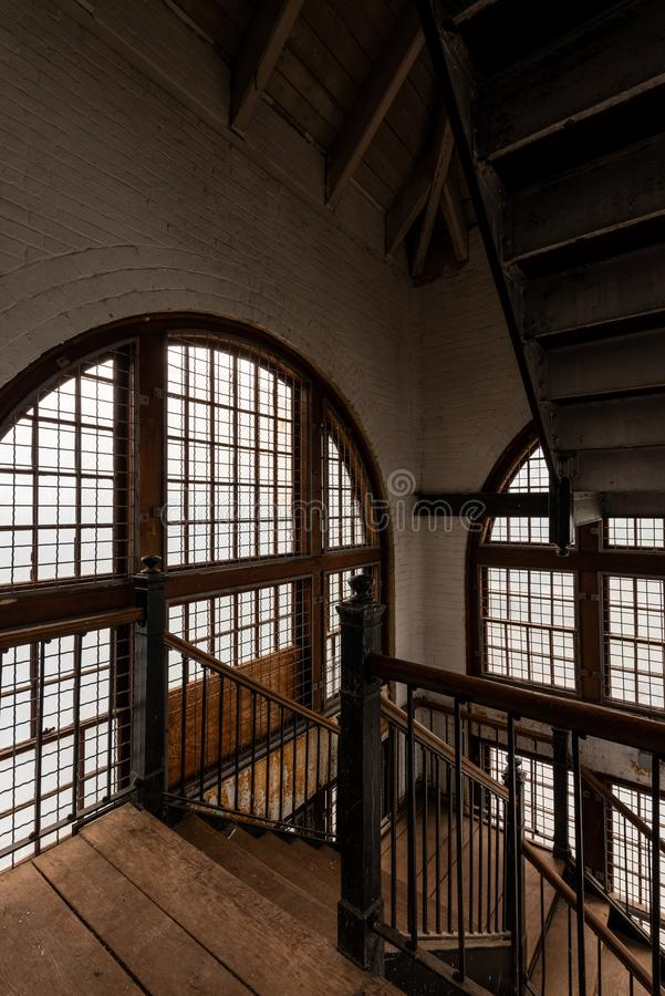 Intricate Cast Iron Staircase & Large Windows - Abandoned Tewksbury State Hospital - Massachusetts. A portrait view of an intricate cast iron staircase and large royalty free stock image