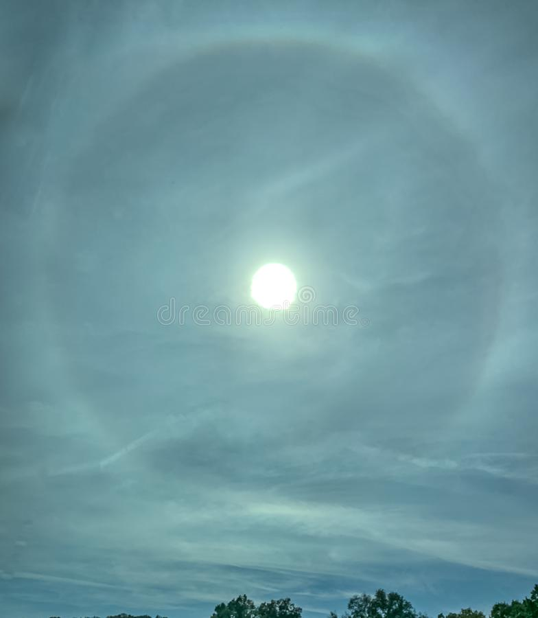 Portrait view of stunning sun halo over tree-lined landscape. stock image