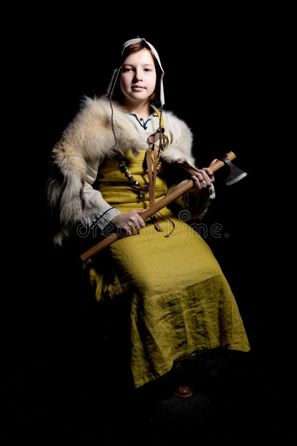 Portrait of a Viking teenage girl dressed in ancient clothes of white and yellow color, created from archaeological finds, 10-11 c. Teenager girl posing in royalty free stock photo