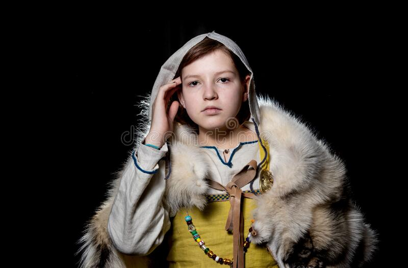 Teenager girl posing in ancient Viking clothes - Hangerok. On her shoulders is the skin of a wolf. Close-up. Portrait of a Viking teenage girl dressed in ancient royalty free stock image