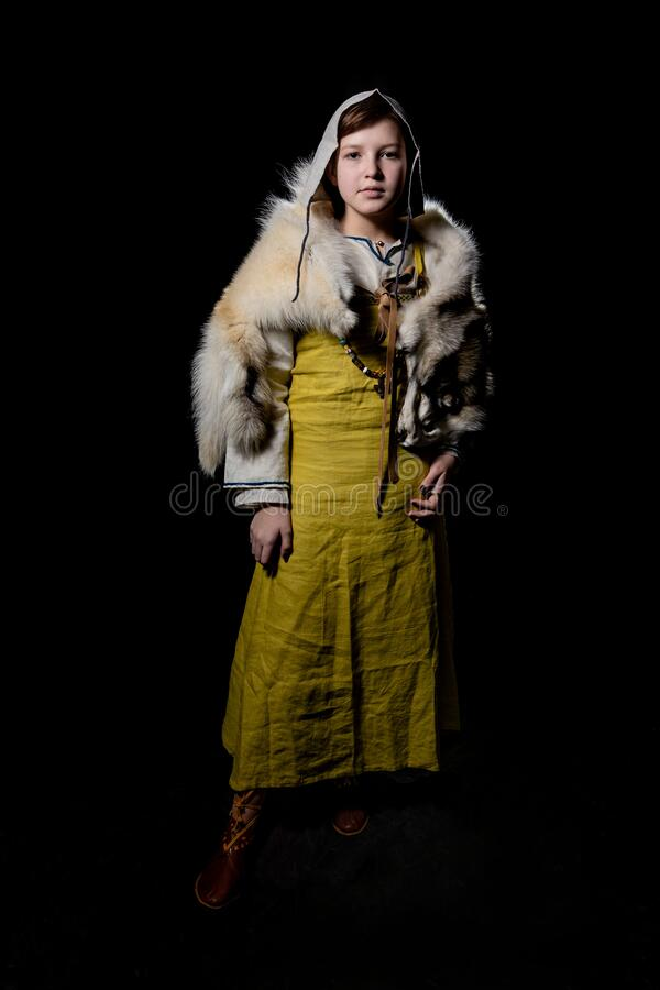 Teenager girl posing in ancient Viking clothes - Hangerok. On her shoulders is the skin of a wolf. Full height. Portrait of a Viking teenage girl dressed in royalty free stock images
