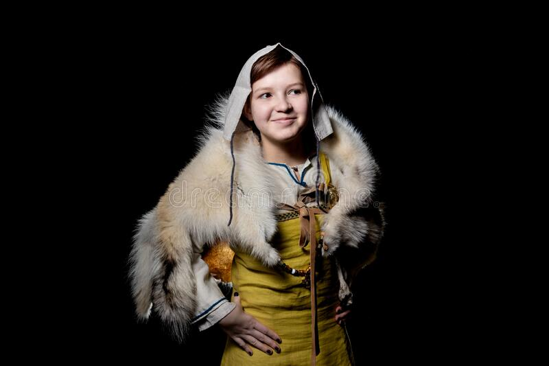 Teenager girl posing in ancient Viking clothes - Hangerok. On her shoulders is the skin of a wolf. The girl smiles, a waist-high p. Portrait of a Viking teenage royalty free stock photos