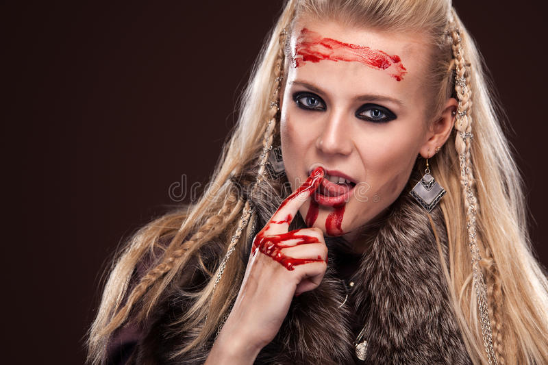 Portrait of viking woman in a traditional warrior clothes. Face in blood. royalty free stock photo