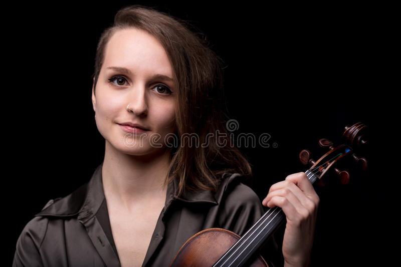 Portrait of a violinist woman. Formal portrait of a young violinist woman on black background stock image