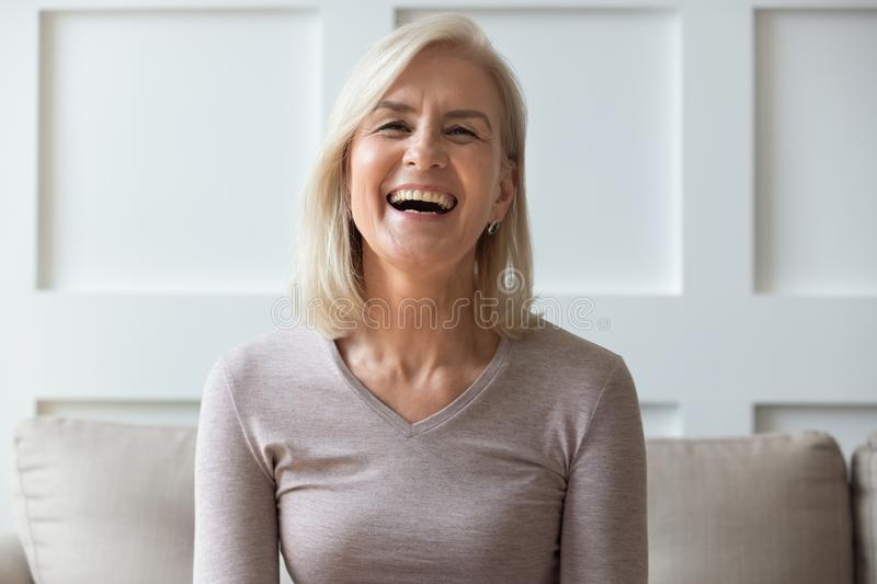 Portrait vivacious elderly woman sit on couch look at camera. Vivacious elderly 60s blond woman with wide toothy candid smile sit on sofa look at camera head stock image