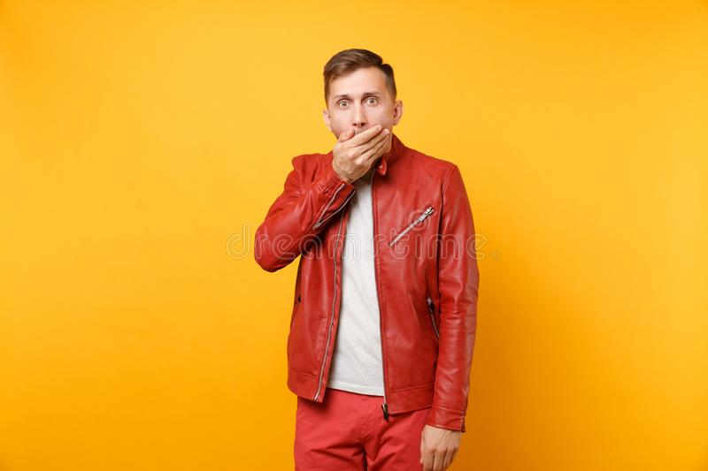 Portrait vogue shocked handsome young man 25-30 years in red leather jacket, t-shirt standing isolated on bright stock photo