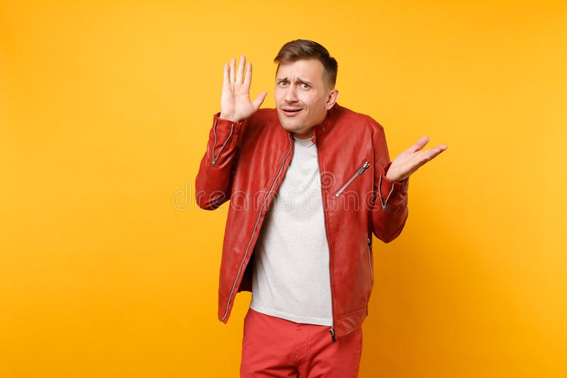 Portrait vogue shocked handsome young man 25-30 years in red leather jacket, t-shirt standing isolated on bright stock image