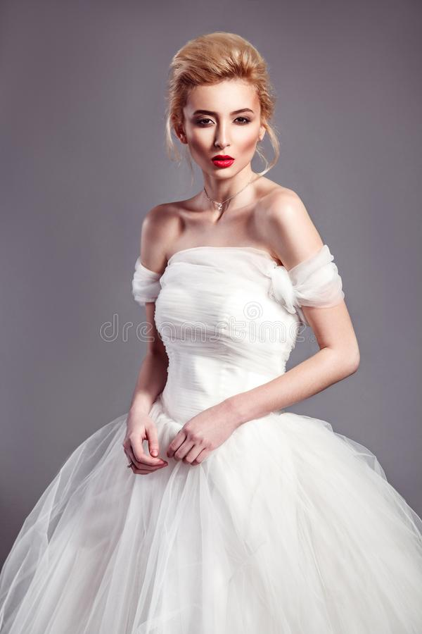 Portrait in vogue style of fashion beautiful bride in wedding dr. Ess posing on grey background royalty free stock images