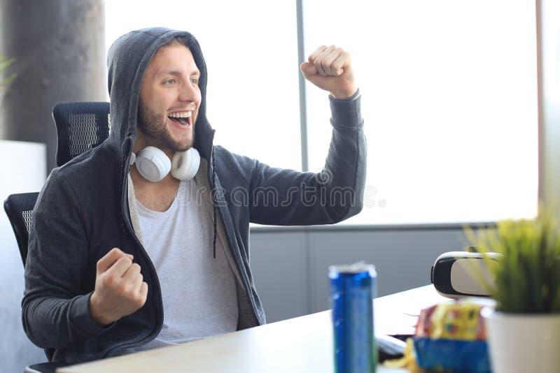 Portrait von ecstatischen Gamer-Typen in Kopfhörern schreien und jubeln beim Spielen von Videospielen auf dem Computer stockfotos
