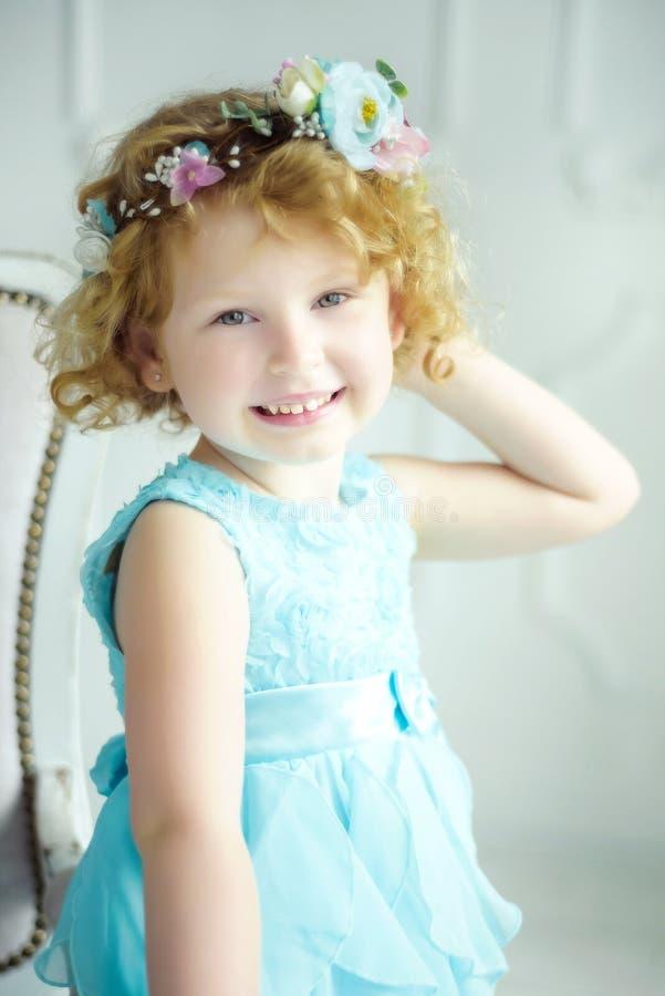 Portrait von 5 Jahre alt, lockig blond lächelnd Mädchen in blauem Kleid und Kranz Frühling kommt kleines Mädchenporträt im Studio lizenzfreie stockbilder