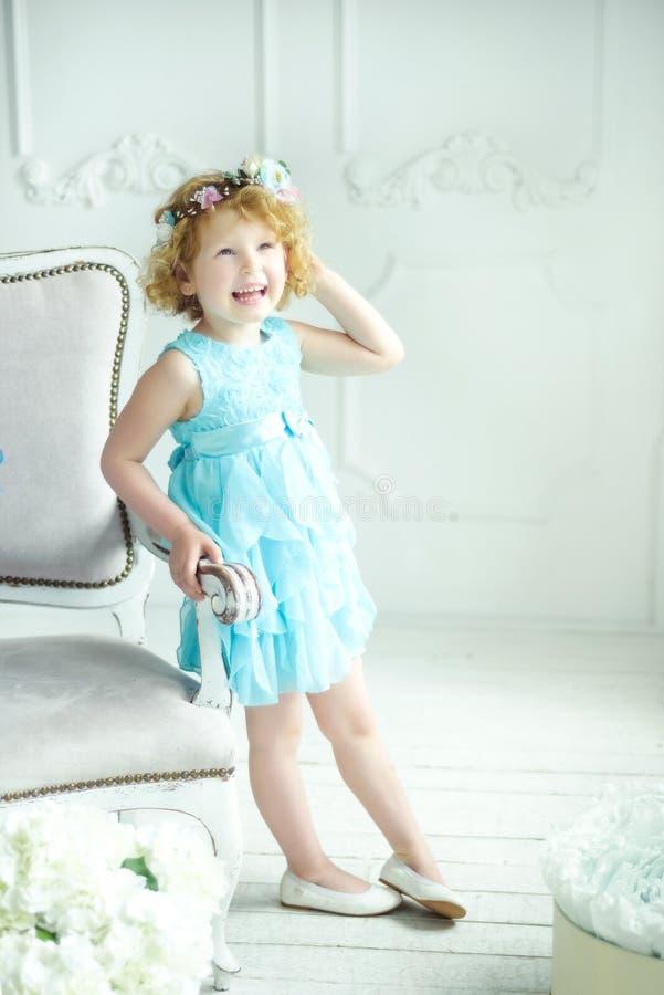 Portrait von 5 Jahre alt, lockig blond lächelnd Mädchen in blauem Kleid und Kranz Kleines Mädchen bleibt im Studio mit natürliche stockfoto