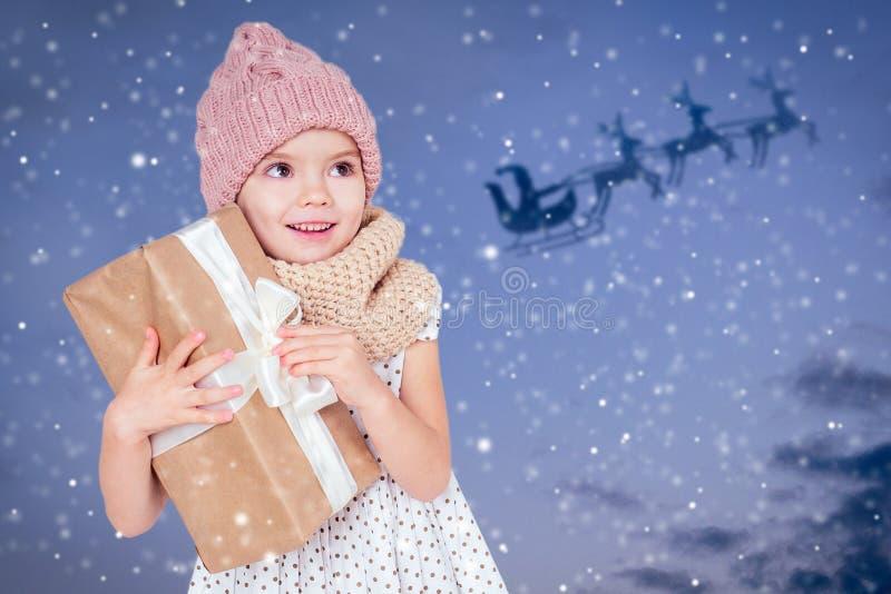 Portrait von kleinen Mädchen mit Geschenk in einem gestrickten Hut auf dunkelblauem Hintergrund Cute blonde Kind mit Weihnachtsge stockbilder