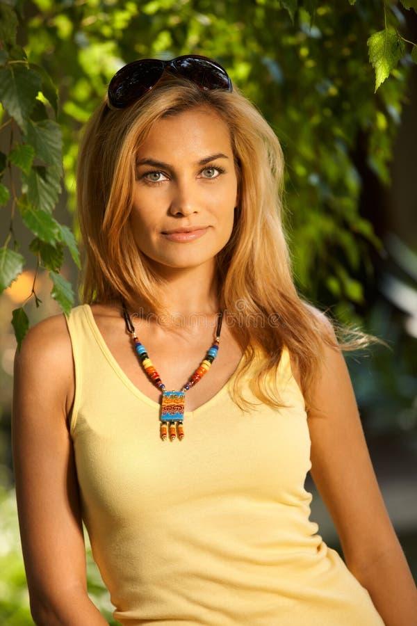 Portrait von schönem blondem im Garten lizenzfreie stockfotos