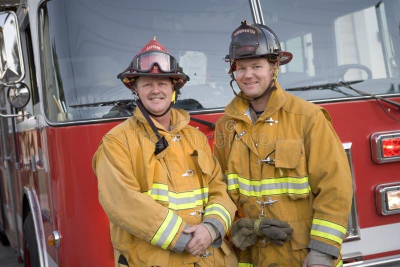 Portrait von zwei Feuerwehrmännern durch ein Löschfahrzeug stockbilder