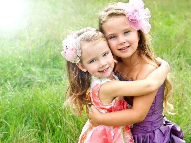 Portrait von zwei umfassenden netten kleinen Mädchen lizenzfreie stockbilder